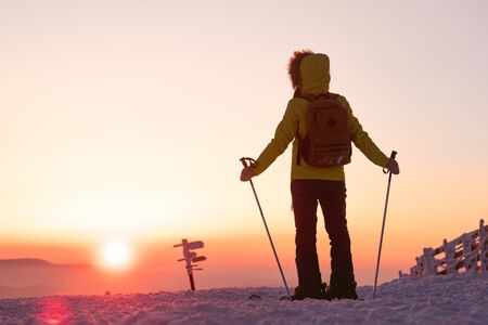 Skier girl stands with ski poles against sunset sky. Ski vacations or resort concept Imagens