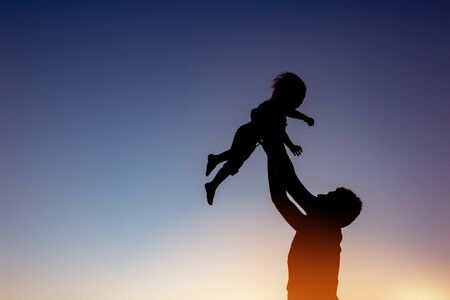 Fathers and son care concept with two silhouettes playing against sunset sky