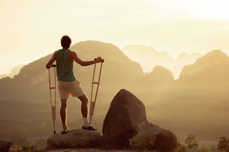 Injured man stands with crutches on big rock. Travel for disabled peoples concept Imagens