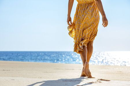 Slim young girl in yellow dress walks at white sandy beach with blue water