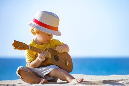 Pretty kid plays on ukulele or small guitar at white sandy beach with blue water Imagens