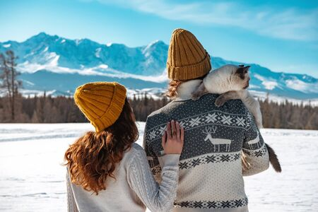 Young couple with cat on shoulder stands in sweaters and knitted hats against mountains Imagens
