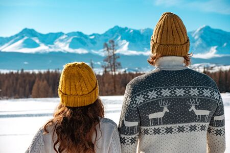 Young couple in sweaters and knitted hats stands against mountains