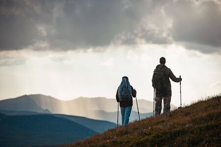 Couple of unrecognised hikers silhouettes stands with trekking poles in mountains Imagens