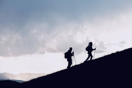 Two hikers silhouettes goes together uphill in mountains against clouds Imagens