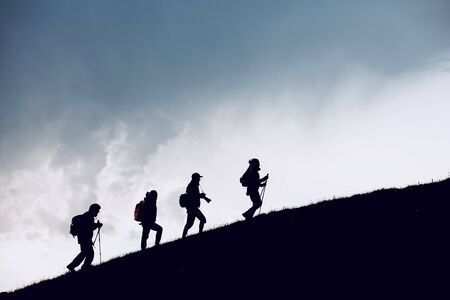 Group of four hikers silhouettes are going uphill in mountains against cloudy sky