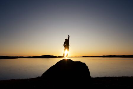 Mans silhouette jumps on big rock against sunset lake and mountains