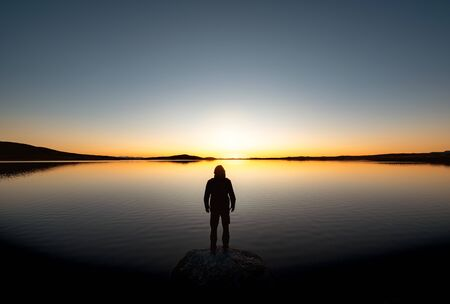 Lonely mans silhouette stands on big rock at sunset lake and looks on mountains