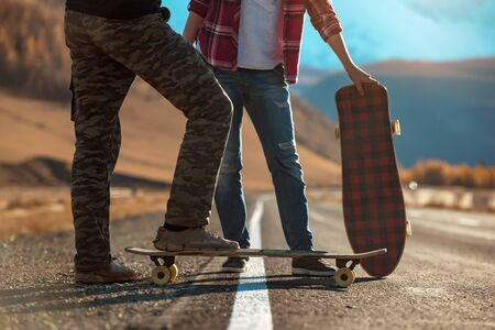 Two young longboarders stands with longboards on straight mountains road Imagens