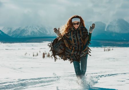Young happy girl dressed in poncho runs in powder snow in mountains area Zdjęcie Seryjne
