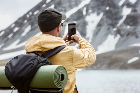 Male hiker takes mobile photo of mountain lake. Travel photography concept