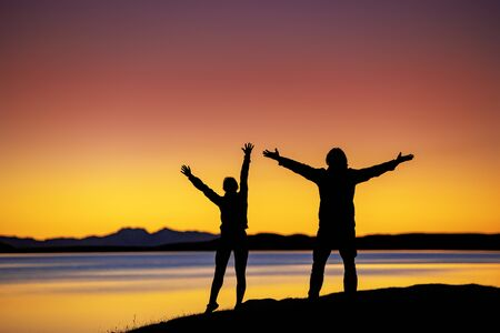 Silhouettes of two hikers stands in winner pose with raised arms against sunset lake and mountains