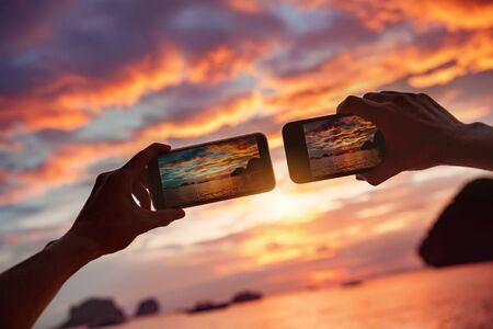 Two hands with mobile phones takes photo of beautiful sea bay sunset Imagens