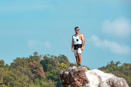 Sporty strong man is standing on big rock at mountain top against blue sky and forest