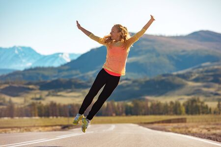 Happy sporty girl jumps on straight mountain road