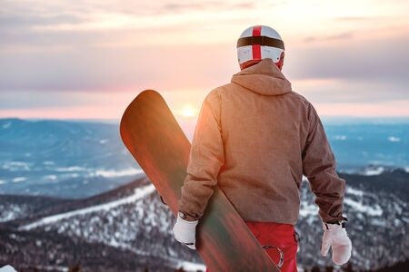Snowboarder stands with snowboard in hands against sunset and mountains Imagens