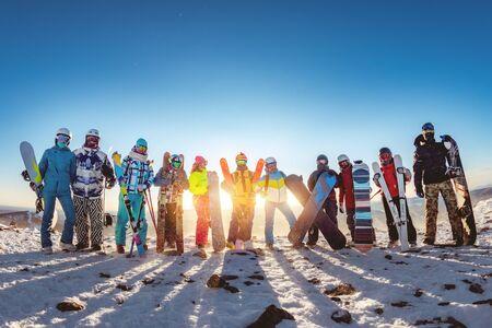 Große Gruppe von Freunden Skifahrer und Snowboarder posieren mit Ausrüstung am Sonnenuntergangsberg