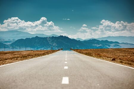 Very hot straight desert road with miracles against blue mountains and cloudy sky