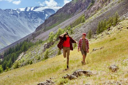 Happy couple of young hipsters are walking in mountains Imagens