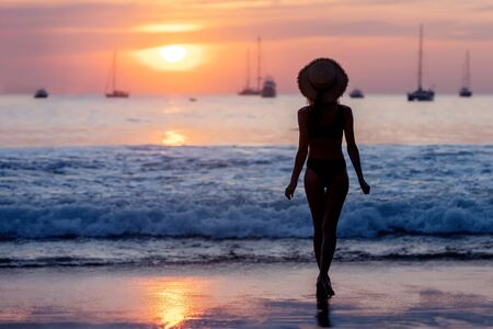 Beautiful silhouette of slim girl is standing against sunset beach and sky