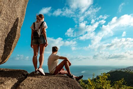 Beautiful couple of hikers stands on big rock at mountain and looking at sea and jungle Imagens