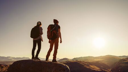 Two travelers or hikers are standing at sunset time on big rock in mountains area