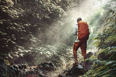 Traveler or hiker with backpack stands in waterfall water dust against sunlight and jungle