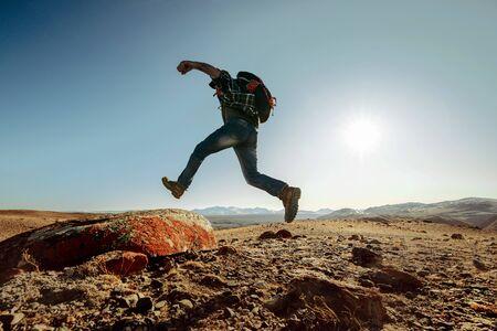 Hiker or traveler with backpack jumps on big rock against blue sunset sky