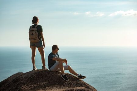 Couple of young hikers are relaxing on big rock against sea and sky