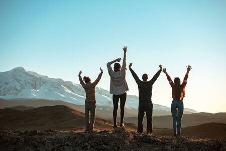 Four happy friends are standing with raised arms and looking at sunset mountains and sky. Unrecognized peoples