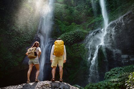 Couple of travelers or hikers with backpacks are standing on big rock and enjoying big waterfall Banco de Imagens