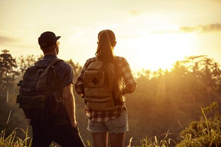 Couple of travelers stands with backpacks and looks at sunrise in tropics