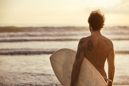 Athletic man surfer stands with blank white surfboard at sunset ocean beach Banco de Imagens
