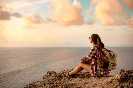 Girl traveler with backpack sits on the cliff against sea and looks at sunset