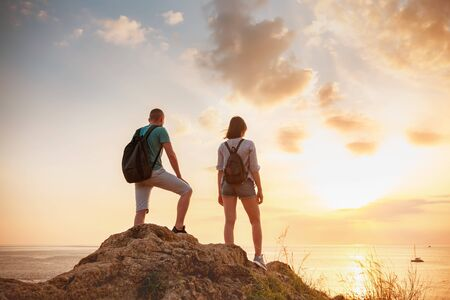 Two young hikers male and female are standing on big rock and looking at sunset sea and sky