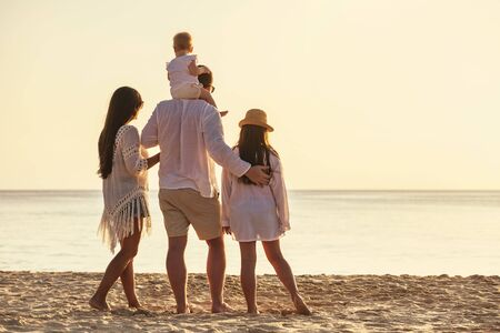 Family of four unrecognizable people are standing with small daughters at sunset sea beach 免版税图像