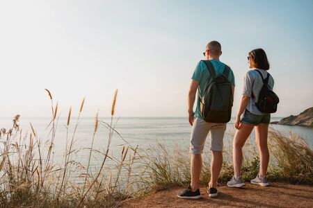 Couple of young hikers with backpacks are standing at sea view point and enjoys sunset 免版税图像