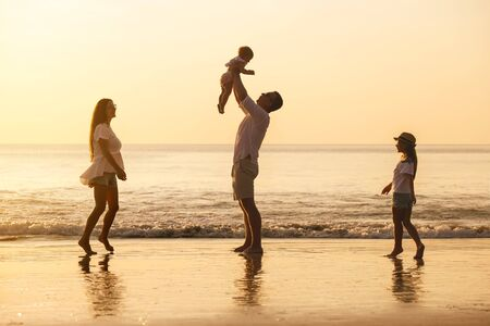 Happy family with two young daughters are playing on sunset sea beach