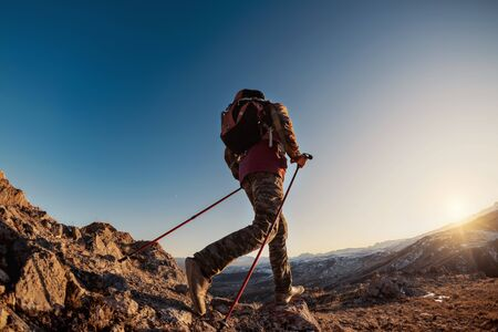 Hiker with backpack walks or explores the mountains at sunset time
