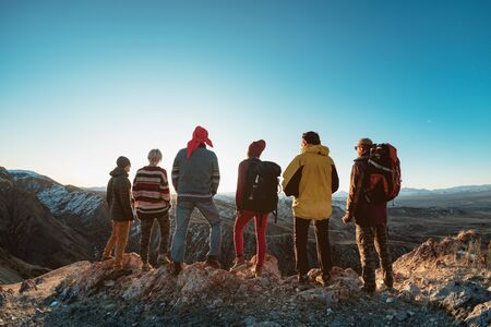 Group of hikers are standing on mountain top and looking at sunset
