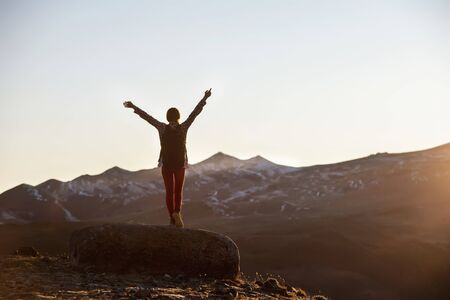 Happy female hiker with backpack stands with raised arms on big rock and looks on mountains and sunset