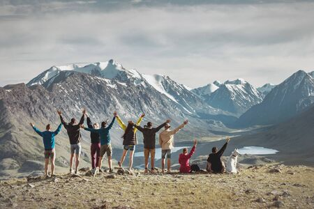 Big group of happy young hikers are standing with raised arms in mountains 免版税图像