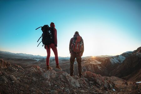 Couple of young hikers with big backpacks are standing and looking at mountains and sunset