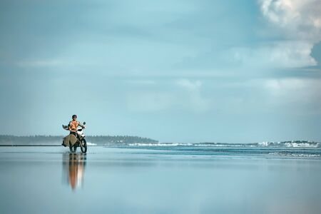 Authentic male surfer rides with surfboard on motorcycle at ocean beach. Real Bali surfing photo