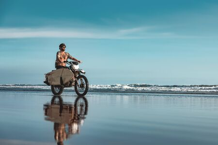 Real Bali male surfer rides on motorcycle with surfboard by ocean beach