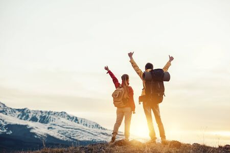 Two happy hikers with backpacks are standing with raised arms and looking at mountains and sunset