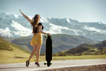 Young girl is standing with longboard at mountain road 免版税图像