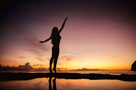 Happy woman in swimsuit stands with raised arms at sunset sea beach
