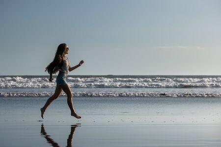 Happy beautiful girl runs alone at ocean beach