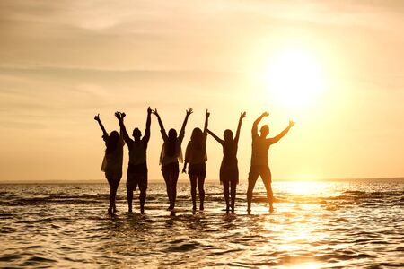 Group of young peoples is standing in water and greetings sunset with raised arms 免版税图像